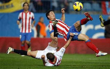Atletico Madrid's Cristian ''Cebolla'' Rodriguez (top) kicks the ball over Sevilla's Fernando Navarro during their Spanish first division soccer match at Vicente Calderon stadium in Madrid November 25, 2012. REUTERS/Sergio Perez