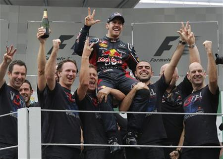 Red Bull Formula One driver Sebastian Vettel of Germany (C) celebrates winning the world championship with Technical Chief Adrian Newey (R) and Team Principal Chrisian Horner (3rd L) after the Brazilian F1 Grand Prix at Interlagos circuit in Sao Paulo November 25, 2012. REUTERS/Sergio Moraes