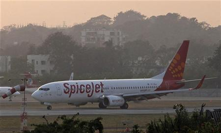 A SpiceJet aircraft taxis on the tarmac after landing at Chhatrapati Shivaji international airport in Mumbai November 26, 2012. Struggling carriers Jet Airways India Ltd and SpiceJet Ltd are in talks with Abu Dhabi's Etihad Airways and Malaysia's AirAsia Bhd to sell minority stakes, a senior government official with direct knowledge of the talks said. REUTERS/Danish Siddiqui