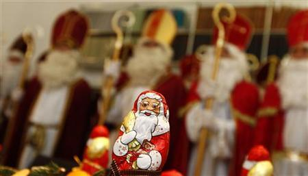 Tax and legal professionals dressed in St. Nicholas costumes are pictured behind a chocolate Santa Claus, during a meeting to receive instructions for their participation in St. Nicholas Day festivities, in Munich November 8, 2012. Each year a group of volunteers made up of tax consultants, lawyers, a school director and an orthodontist, dress-up as St. Nicholas to distribute sweets and small presents to children to celebrate St. Nicholas Day. Over two-days the 24 St. Nicholas' will visit 70 families, social projects and orphanages in Munich with private donations. St. Nicholas Day is traditionally celebrated on December 6. Picture taken November 8. REUTERS/Michaela Rehle (GERMANY - Tags: RELIGION SOCIETY)