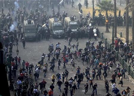 Protesters run from the riot police during clashes at Tahrir square in Cairo November 25, 2012. Egyptian President Mohamed Mursi's decree that put his decisions above legal challenge until a new parliament was elected caused fury amongst his opponents on Friday who accused him of being the new Hosni Mubarak and hijacking the revolution. Police fired tear gas in a street leading to Cairo's Tahrir Square, heart of the 2011 anti-Mubarak uprising, where thousands demanded Mursi quit and accused him of launching a ''coup''. There were violent protests in Alexandria, Port Said and Suez. REUTERS/Mohamed Abd El Ghany (EGYPT - Tags: CIVIL UNREST POLITICS)