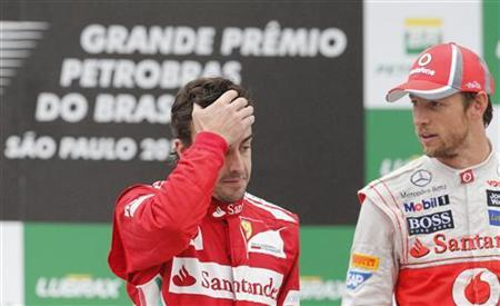 Second placed Ferrari Formula One driver Fernando Alonso of Spain (L) gestures next to race winner McLaren driver Jenson Button of Britain on the podium after the Brazilian F1 Grand Prix at Interlagos circuit in Sao Paulo November 25, 2012. REUTERS/Paulo Whitaker