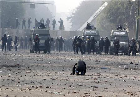 A protester kneels during clashes in Cairo November 25, 2012. REUTERS/Mohamed Abd El Ghany