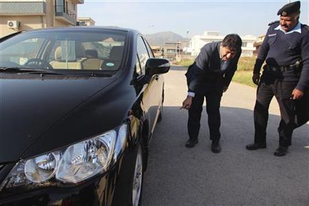 Senior journalist for the Geo News television station Hamid Mir points to his car where a bomb was found underneath, in Islamabad November 26, 2012. REUTERS/Sohail Shahzad