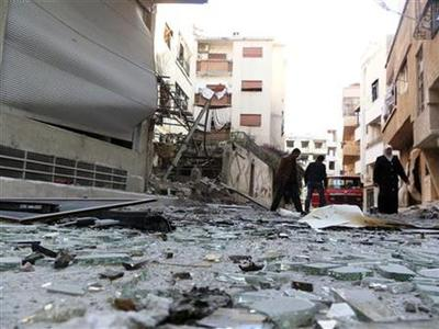 Residents walk near debris from damaged buildings after shelling by forces loyal to Syria's President Bashar al-Assad at Daria near Damascus November 26, 2012. REUTERS/Fadi al-Derani/Shaam News Network/Handout