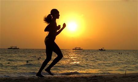 A woman runs along Seven Mile Beach in George Town, Cayman Islands, April 27, 2010. REUTERS/Gary Hershorn/Files