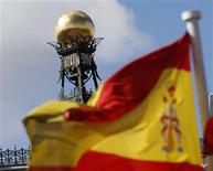A Spanish flag flutters in the wind in front of the dome of Bank of Spain headquarters in central Madrid September 24, 2012. Spain once pushed hard for Ireland and Portugal to ask for bailouts from their partners in the euro because it was keen to shelter itself from an accelerating sovereign debt crisis. Now the tables are turned and Madrid is holding back from applying for help, not least because the Spanish government knows all too well what befell its Portuguese and Irish peers once they did seek help -- voters dumped them. REUTERS/Sergio Perez (SPAIN - Tags: POLITICS BUSINESS)