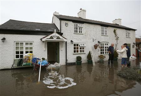 Residents speak outside a flooded house, close to the River Trent in Willington, central England, November 26, 2012. REUTERS/Darren Staples
