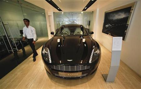 An employee walks past an Aston Martin Rapide inside the company's showroom in Mumbai January 2, 2012. REUTERS/Danish Siddiqui/Files