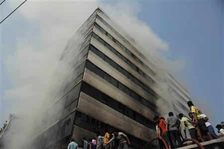Fire fighters try to control a fire as smoke engulfs an 11-storey garment factory building in the suburb of Uttara in Dhaka November 26, 2012. REUTERS/Stringer