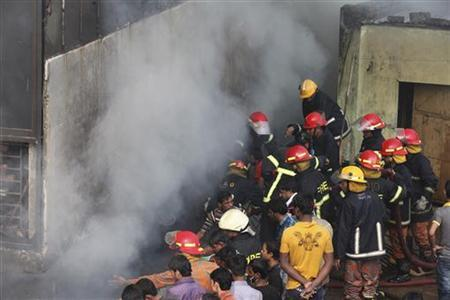 Fire fighters try to control a fire as smoke engulfs an 11-storey garment factory building in the suburb of Uttara in Dhaka November 26, 2012. A fire brigade official said the blaze in the building in the suburb of Uttara, which housed three separate factories, was almost under control. There were no reports of deaths, but eight workers were injured due to heavy smoke, fire brigade Director General Abu Nayeem Mohammad Shahidullah told Reuters. REUTERS/Stringer