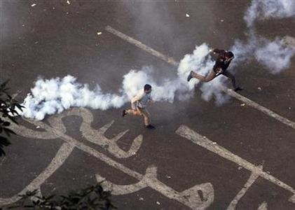 Protesters run away from tear gas with the characters ''Leave Mursi'' written under them in Cairo November 25, 2012. REUTERS/Mohamed Abd El Ghany