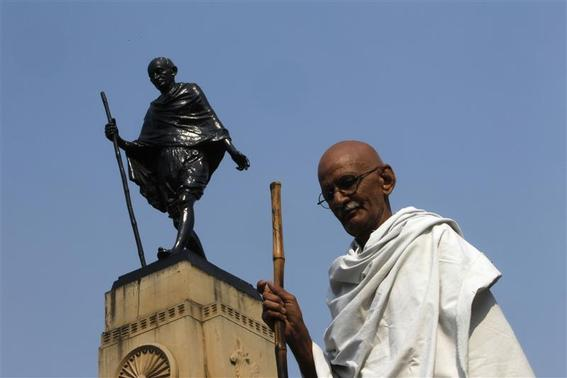Mahesh Chaturvedi, 63, who dresses up like Mahatma Gandhi, poses for a photo in front of a statue of Gandhi in the old quarters of New Delhi, October 25, 2012. REUTERS/Mansi Thapliyal