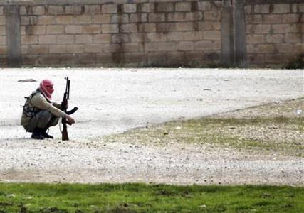 A member of the Free Syrian Army waits as gunfire is heard between them and the armed Kurds of The Kurdish Democratic Union Party (PYD) in the northern Syrian town of Ras al-Ain, November 25, 2012. Iran said Turkey's plans to deploy Patriot defensive missiles near its border with Syria would add to the region's problems, as fears grow of the Syrian civil war spilling across frontiers. REUTERS/Amr Abdallah Dalsh