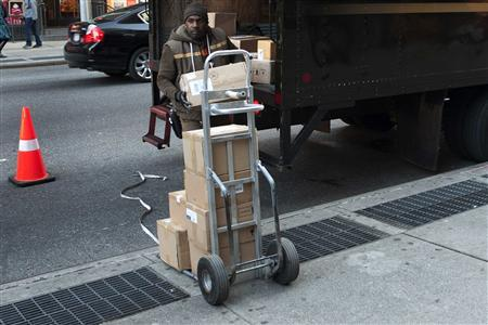 A UPS delivery man unloads boxes from a truck in New York November 26, 2012. Cyber Monday's online sales got off to a brisk start, sending e-commerce retailers' shares higher and suggesting strong growth from earlier in the holiday shopping season would continue through December. REUTERS/Keith Bedford