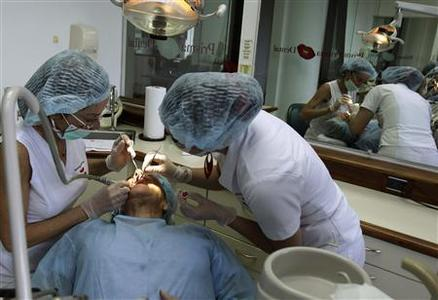 Two dentists work on a U.S. patient at a dental clinic in San Jose, November 1, 2012. Around 40,000 medical tourists visited Costa Rica last year, compared to 36,000 in 2010 and 30,000 in 2009. Most of them are American and Canadian, according to the country's tourism institute, ICT. Of that number, almost 15,000 of them traveled for dental care, said Massimo Manzi, director at Promed, the council for international promotion of medicine in Costa Rica. Picture taken November 1, 2012. REUTERS/Juan Carlos Ulate