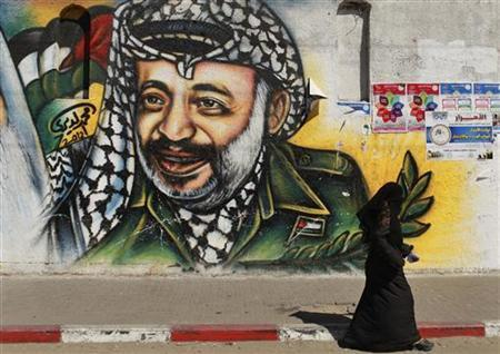 A Palestinian woman walks past a mural depicting late leader Yasser Arafat (R) in Gaza City July 4, 2012. The Palestinian Authority agreed on Wednesday to the exhumation of Arafat's body after new allegations that he was poisoned with the radioactive element polonium-210 in 2004. REUTERS/Mohammed Salem