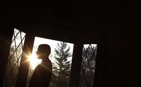 Parker Roos, who suffers from Fragile X, watches television as the sun rises and shines through the window at his home in Canton, Illinois, April 4, 2012. REUTERS/Jim Young/Files