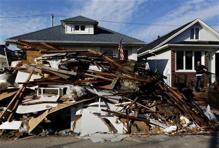A man carries debris from a home in Long Beach, New York November 26, 2012. REUTERS/Shannon Stapleton