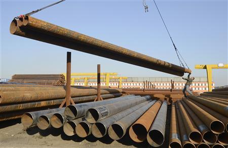 A labourer works to hook steel pipes onto a crane at a steel market in Taiyuan, Shanxi province, October 17, 2012. REUTERS/Jon Woo