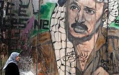 Un equipo internacional de expertos exhumó el martes el cuerpo del fallecido líder palestino Yaser Arafat, en un intento por descubrir si fue envenenado tal y como creen muchos palestinos. En la imagen, una palestina camina frente a un mural sobre el polémico muro israelí que retrata al fallecido líder palestino Yaser Arafat, en el punto de control de Qalandiya, cerca de la ciudad cisjordana de Ramala, el 26 de noviembre de 2012. REUTERS/Marko Djurica