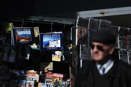 A man walks past a kiosk selling newspapers and magazines in Athens November 26, 2012. REUTERS-Yorgos Karahalis
