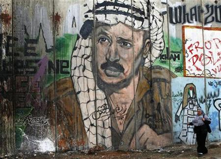 A Palestinian woman walks past a mural on the controversial Israeli barrier depicting the late Palestinian leader Yasser Arafat, at Qalandiya checkpoint near the West Bank city of Ramallah November 26, 2012. The body of Arafat will be exhumed on Tuesday, eight years after his death, in an investigation to establish if he was murdered, a Palestinian official said on Saturday. REUTERS/Marko Djurica (WEST BANK - Tags: OBITUARY POLITICS)
