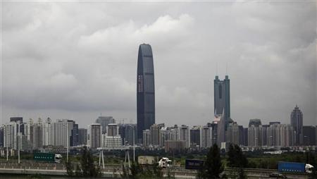 Container trucks cross a bridge in front of the 100-floor Kingkey 100, the tallest building in downtown Shenzhen neighboring Hong Kong, May 16, 2012. REUTERS/Bobby Yip