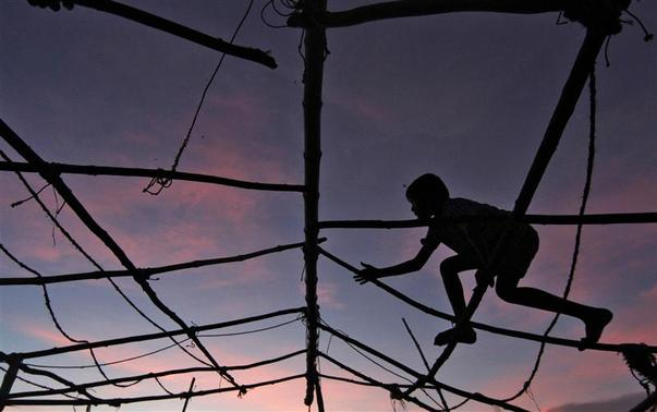 A boy is silhouetted against the setting sunlight as he plays over a damaged hut at Marina beach in Chennai November 7, 2012. REUTERS/Babu