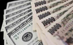 El euro alcanzó un máximo de un mes en Asia contra el dólar después de alcanzarse un acuerdo sobre un nuevo objetivo de deuda para Grecia, pero las ganancias fueron efímeras por haberse cotizado con anterioridad la probabilidad de un acuerdo. En esta imagen de archivo, una fotografía ilustrativa muestra billetes de 100 dólares y de 10.000 yenes en Tokio, el 2 de agosto de 2011. REUTERS/Yuriko Nakao