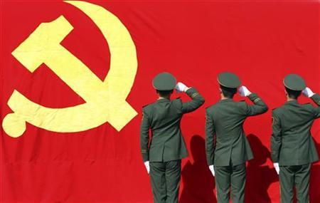 Paramilitary policemen hold their fists in front of a flag of Communist Party of China as they attend an oath-taking rally to ensure the safety of the upcoming 18th National Congress of the Communist Party of China (CPC), at a military base in Hangzhou, Zhejiang province November 5, 2012. REUTERS/China Daily
