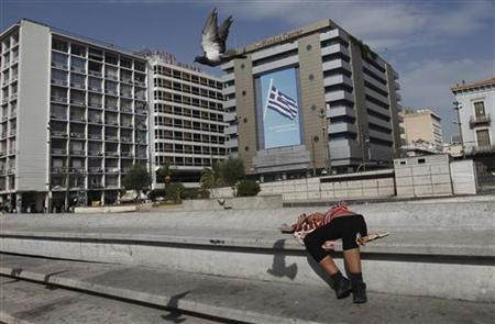 A woman lies at central Omonia Square in Athens October 17, 2012. REUTERS/John Kolesidis