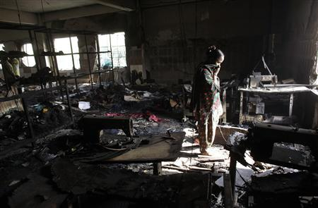 A worker visits a burnt garment factory after a fire which killed more than a hundred people, in Savar November 26, 2012. Thousands of angry textile workers demonstrated in the outskirts of Dhaka on Monday after a fire swept through a garment workshop at the weekend, killing more than 100 people in Bangladesh's worst-ever factory blaze. REUTERS/Andrew Biraj