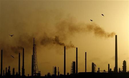 The sun sets behind Isla refinery in Willemstad at the island of Curacao June 16, 2008. REUTERS/Jorge Silva/Files