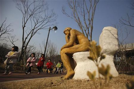 Kindergarten children walk past an installation shaped like Auguste Rodin's ''The thinker'' sat on a toilet at the Toilet Culture Park in Suwon, about 46 km (29 miles) south of Seoul, November 22, 2012. REUTERS/Kim Hong-Ji