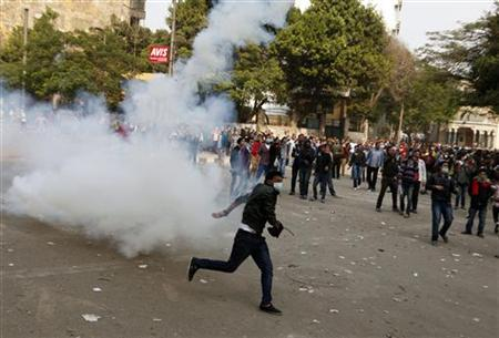 A protester runs to throw a tear gas canister back at police during clashes with police near Tahrir Square as anti-Mursi protesters start to gather in the square in Cairo November 27, 2012. Opponents of President Mohamed Mursi rallied in Cairo's Tahrir Square for a fifth day on Tuesday, stepping up calls to scrap a decree they say threatens Egypt with a new era of autocracy. REUTERS/Asmaa Waguih (EGYPT - Tags: POLITICS CIVIL UNREST)