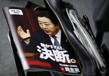 A picture of Japan's Prime Minister Yoshihiko Noda, who is also the leader of the ruling Democratic Party of Japan (DPJ), is seen on the cover of a leaflet of the party election campaign platform, in a reporters' bag at a news conference at the party headquarters in Tokyo November 27, 2012. REUTERS/Shohei Miyano
