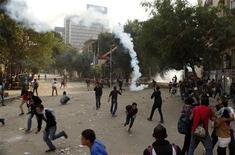 Manifestantes correm para se proteger de gás lacrimogêneo em confrontos com a polícia perto da Praça Tahrir. 27/11/2012 REUTERS/Asmaa Waguih