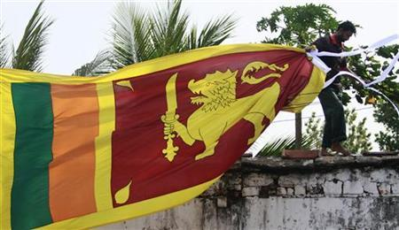 A man climbs up onto a roof to put up the Sri Lankan national flag ahead of celebrations of their 64th Independence day in Colombo February 2, 2012. Sri Lankans will celebrate their Independence day on February 4. REUTERS/Dinuka Liyanawatte/Files