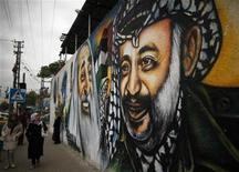 Palestinians walk next to a mural depicting late Palestinian leader Yasser Arafat (R) in Gaza City November 27, 2012. The body of Arafat was exhumed on Tuesday, eight years after his death, as part of an investigation into allegations he was poisoned, official Palestinian radio said. REUTERS/Suhaib Salem (GAZA - Tags: POLITICS)