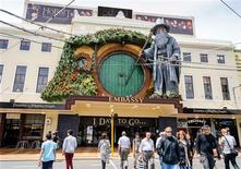 """La capital de Nueva Zelanda se apresuraba a transformarse en un refugio de pies peludos y orejas puntiagudas el martes mientras las estrellas comenzaban a llegar para el muy esperado estreno mundial de la primera película de la trilogía de """"El Hobbit"""". En la imagen, peatones pasan junto a un modelo gigante del personaje de J.R.R. Tolkien Gandalf en la fachada del cine Embassy de Wellington, el 27 de noviembre de 2012. REUTERS/Mark Coote"""