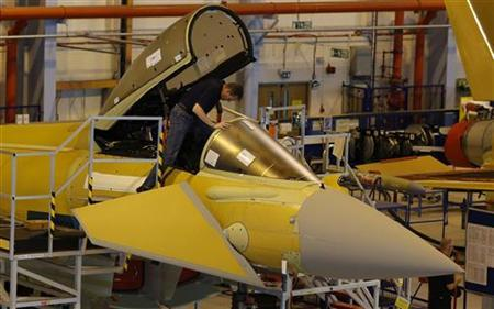 A file photograph shows a member of staff working in the cockpit of an aircraft on the Eurofighter Typhoon production line at BAE systems Warton plant near Preston, northern England September 7, 2012. REUTERS/Phil Noble
