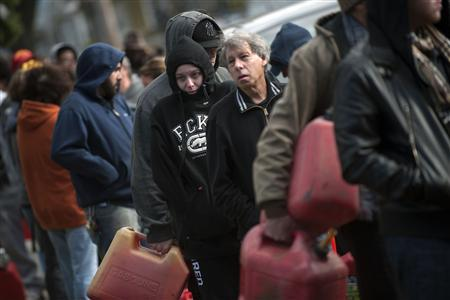 Residents try to keep warm as they line up for gasoline at a temporary fueling station at the National Guard armory in the Staten Island Borough of New York, in this November 3, 2012, file photo. More than 70 percent of filling stations in New York and New Jersey had no gas for sale, according to Travel group AAA. As temperatures dropped to near freezing, supply of heating oil crucial for homes was also strained. REUTERS/Keith Bedford/Files