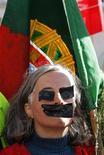 El Parlamento portugués aprobó el martes definitivamente el presupuesto para 2013, que promete un tercer año de recesión y las mayores subidas de impuestos en la historia moderna del país para asegurar que se cumplen los términos del rescate internacional solicitado el año pasado. En la imagen, una mujer con una bandera portuguesa protesta con los ojos y la boca tapada en Lisboa el 27 de noviembre de 2012. REUTERS/Jose Manuel Ribeiro