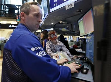 A trader monitors trades as a young boy watches on the floor of the New York Stock Exchange, November 23, 2012. REUTERS/Brendan McDermid