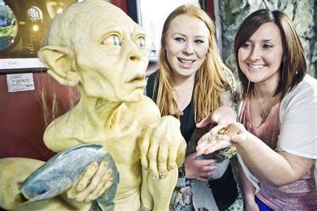 Visitors pose next to a sculpture of the J. R. R. Tolkien character Gollum at the Weta Cave museum in Wellington in this September 25, 2012 handout photograph. New Zealand's capital city was rushing to complete its transformation into a haven for hairy feet and pointed ears on November 27, 2012 as stars jetted in for the long-awaited world premiere of the first movie of the Hobbit trilogy. Picture taken September 25, 2012. REUTERS/Positively Wellington Tourism/Handout