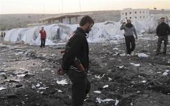 Free Syrian Army (FSA) fighters inspect the damage at an unfinished refugee camp that the FSA says was destroyed by Syrian regime air strikes in Bab Al-Hawa, near the Syria-Turkey border, November 26, 2012. Picture taken November 26, 2012. REUTERS/Abdalghne Karoof