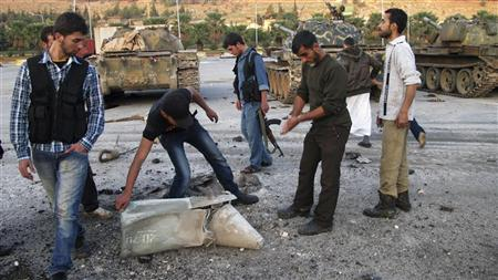Free Syrian Army fighters inspect ammunition that they said was fired by Syrian President Bashar al-Assad's forces at the Free Syrian Army (FSA) base in Bab Al-Hawa, near the Syrian-Turkish border, November 26, 2012. Syrian warplanes bombed two rebel bases near the Turkish border on Monday sending hundreds of people fleeing across the frontier. The attacks on the FSA positions in Atima and nearby Bab al-Hawa came a day before NATO and Ankara were due to start assessing where to station surface-to-air missiles on the Turkish side of the 900-km (560-mile) boundary. Picture taken November 26, 2012. REUTERS/Abdalghne Karoof