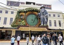 Pedestres passam por modelo gigante do personagem Gandalf, de J. R. R. Tolkien, montado na frente do Teatro da Embaixada em Wellington. A capital da Nova Zelândia estava correndo para completar sua transformação em um paraíso para os seres de pés peludos e orelhas pontudas nesta terça-feira, enquanto as estrelas chegavam para a estreia mundial há muito aguardada do primeiro filme da trilogia Hobbit. 27/11/2012 REUTERS/Mark Coote