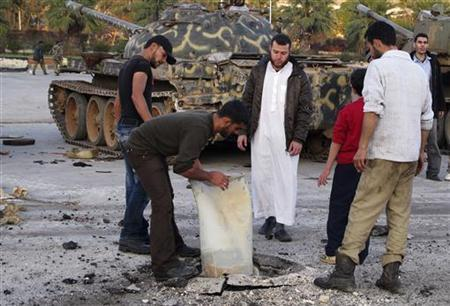 Free Syrian Army fighters inspect ammunition that they said was fired by Syrian President Bashar al-Assad's forces at the Free Syrian Army (FSA) base in Bab Al-Hawa, near the Syrian-Turkish border, November 26, 2012. REUTERS/Abdalghne Karoof
